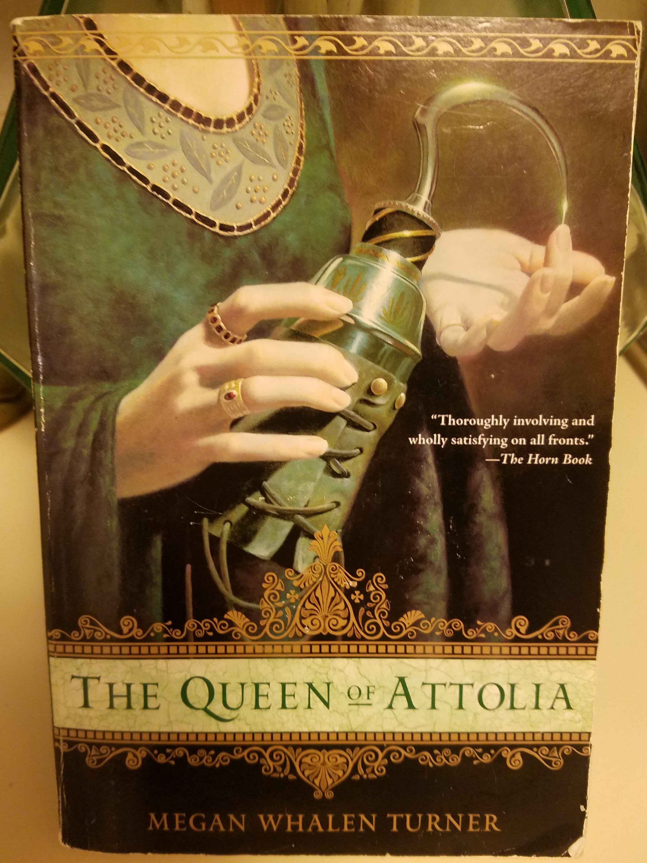 Image description: Book cover for The Queen of Attolia by Megan Whalen Turner. The cover shows the hands and torso of a woman wearing in a medieval-style dress. She is holding a prosthetic hook.