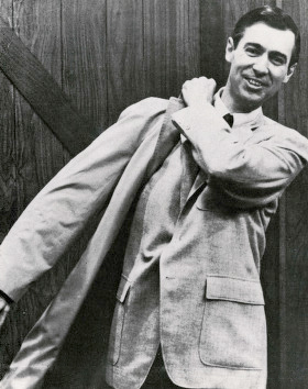 Source: Wikimedia Commons. Description: a black and white image of Fred Rogers smiling at the camera while putting on a coat.