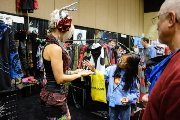 A vendor shows a GGC attendee one of her products.