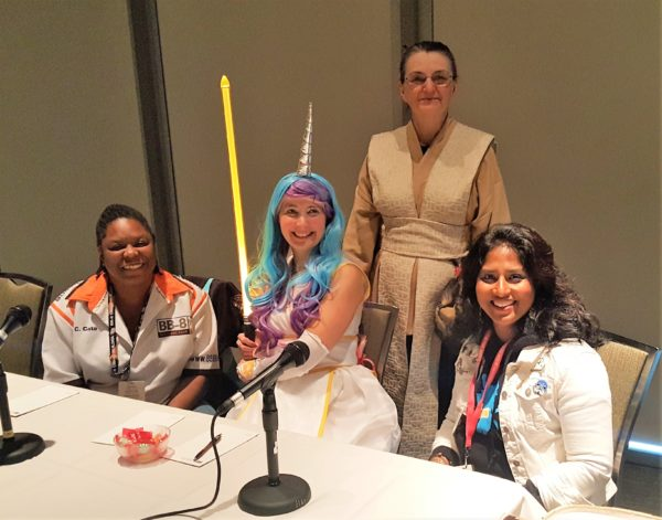 Source: me. Description: Panelists Christina Cato, Pat M. Yulo, Linda Hansen-Raj, and Maggie Nowakowska pose together for a photo. Christina, Pat, and Maggie are all dressed in Star Wars cosplays.
