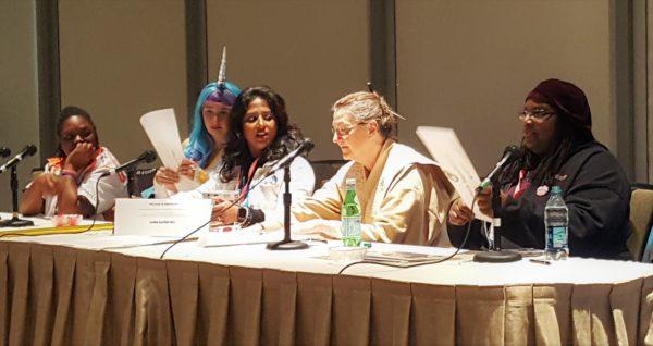 Source: me. Description: Panelists Christina Cato, Pat M. Yulo, Linda Hansen-Raj, Maggie Nowakowska, and Jamala Henderson sitting at the panel table and chatting as they prepare for the panel.