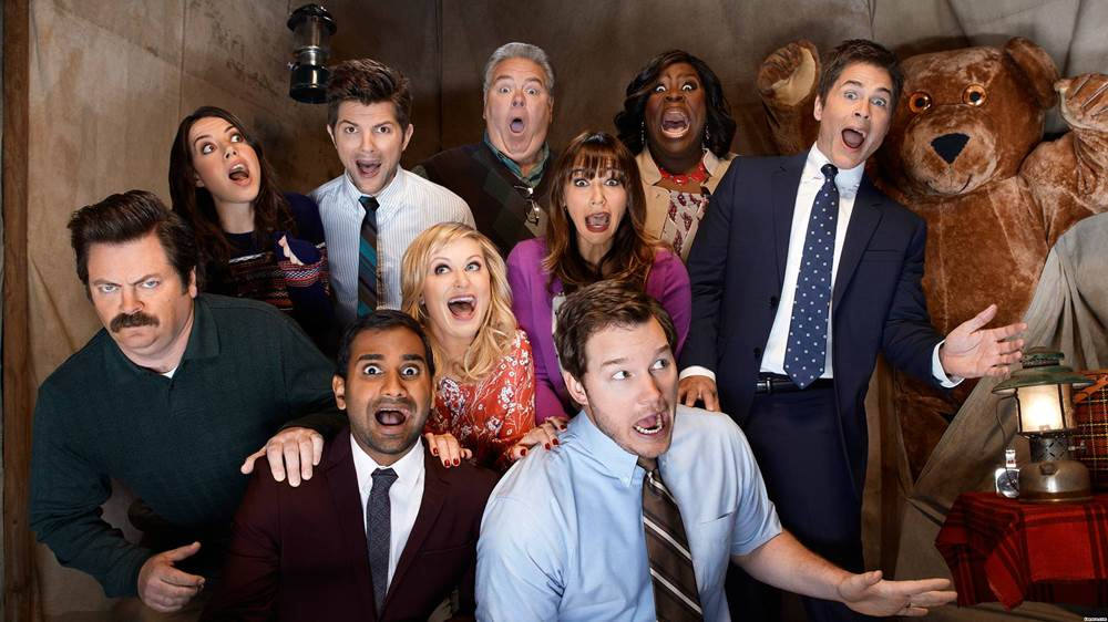Source: Flickr. Description: The cast of Parks and Recreation acting shocked in a tent with a giant stuff teddy bear looming in the background.