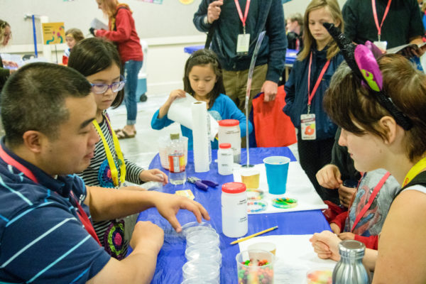 Source: GGC Flickr. Description: A group of adults and children gather around a table of science supplies at the GGC17 DIY Science Zone.