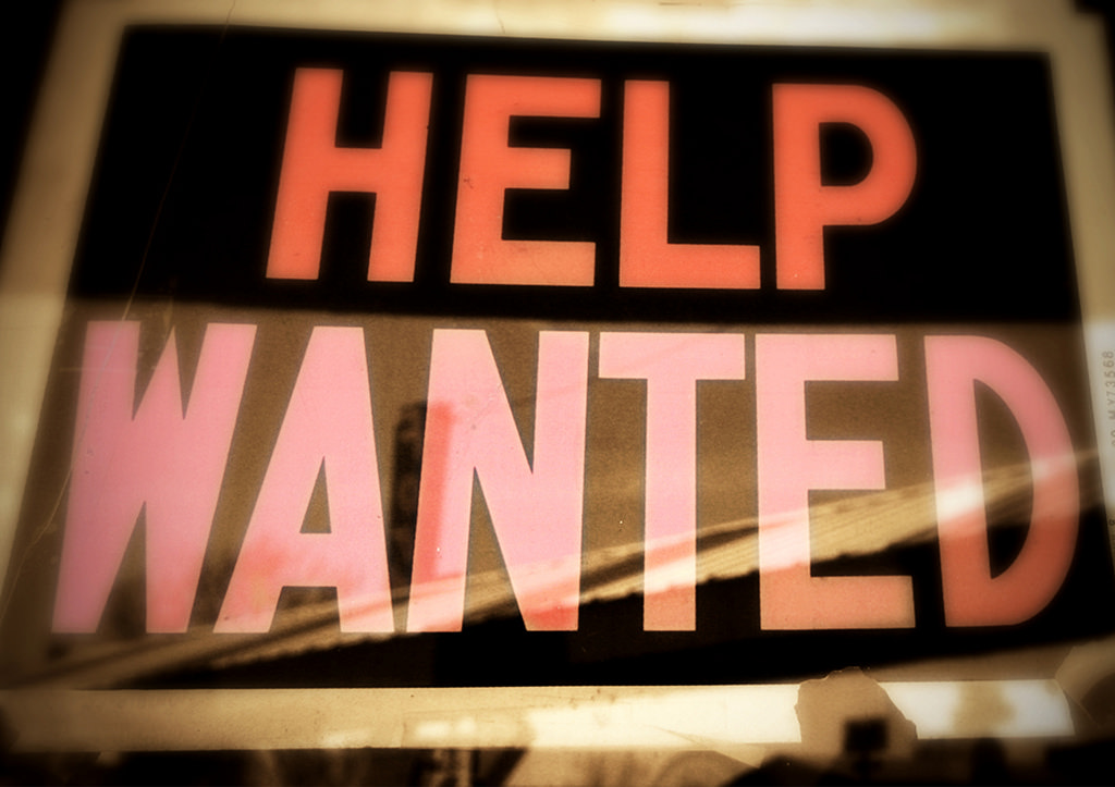 Source: flickr. Description: A picture of a Help Wanted sign in a window.
