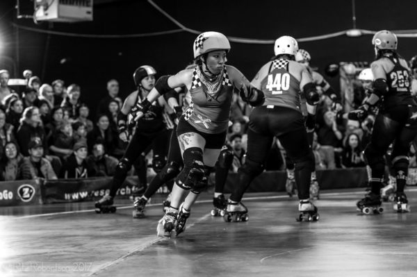 Image description: Jo in roller-skates, elbow and knee pads, and a helmet playing roller derby. Source: R.L. Robertson