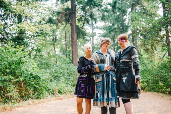 Three people stand in a forest wearing custom clothing designed by Elleveve
