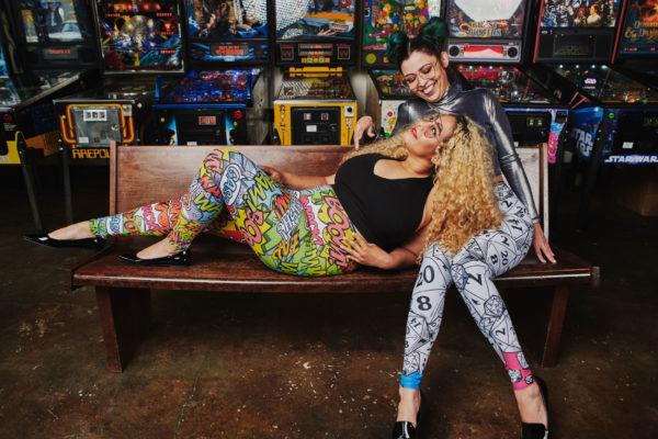 Two women smiling at each other, wearing leggings with comics and gaming patterns designed by Bombsheller