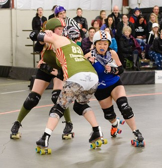 Image description: Jo in roller derby gear and blue lipstick playing with two other girls, also in derby regalia. Source: R.L. Robertson