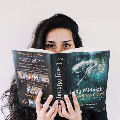 Hannah from A Clockwork Reader holds the book Lady Midnight by Cassandra Clare up so that it covers half her face. Source: The Owlery