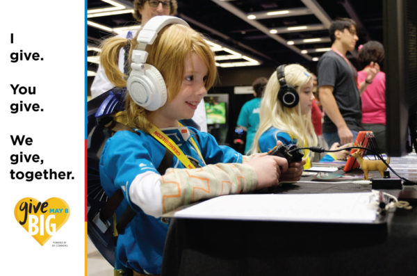 Two girls wearing headphones play a video game while seated at a table at GeekGirlCon. Source: GGC Flickr.