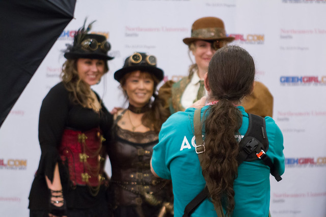 An Agent stands with their back to the camera. They are taking a photo of three Con-goers.