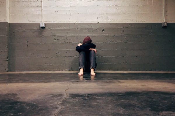 A person sits on a concrete floor alone, their head is hidden in their arms. They're wearing a maroon beanie, black long-sleeve shirt, and jeans. They are barefoot.