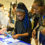 A child and an adult examine items in the DIY Science Zone.